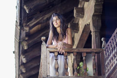 Woman observes the street from a typical wooden balcony Royalty Free Stock Images