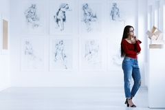 Woman observing contemporary sculpture. In art gallery with drawings. Art gallery concept royalty free stock images