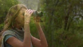 Woman observing the forest using binoculars. Side view of a Caucasian woman Observing the forest using binoculars stock footage