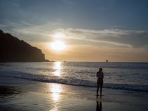 Woman observing the setting sun over the Pacific Ocean stock photography