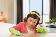 Obsessing compulsive disorder. Woman with obsessing compulsive disorder wiping stain off from the table surface Stock Photo