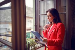 Woman occupied with job working near window. Serious woman occupied with job working near window royalty free stock photography