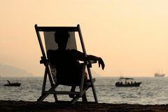 Woman by the ocean. Woman sitting in the chair watching sunset at the beach Royalty Free Stock Photography