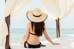 Woman in ocean vacation sitting in beach tent Royalty Free Stock Image