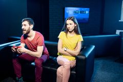 Woman offended by a boyfriend playing video games royalty free stock photo