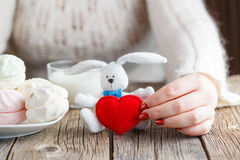 Woman offer red toy heart and eat sweets Stock Images