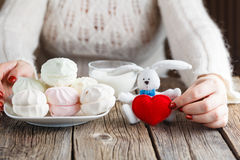 Woman offer red toy heart and eat sweets Stock Photos