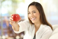Woman offering an apple and looking at camera. Happy woman offering an apple and looking at camera sitting on a sofa in the living room in a house interior Royalty Free Stock Image
