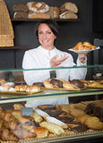 Woman offering deserts in the pastry shop Stock Photo