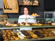 Woman offering deserts in the pastry shop Royalty Free Stock Photos