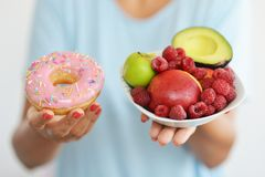 Woman offering different alternative of food, fresh fruits and unhealthy donut royalty free stock images
