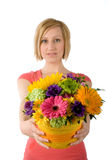 Woman offering flower bouquet. Waist-up portrait of a beautiful young woman giving a bouquet of colorful flowers. Isolated on white background. Focus is on the Royalty Free Stock Photos