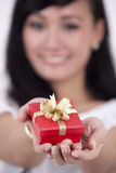 Woman offering a gift. Beautiful woman offering a gift shot with shallow depth of field Stock Photo