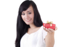 Woman offering a gift. Beautiful woman offering a gift shot with shallow depth of field Royalty Free Stock Photo