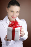 Woman offering a gift. Happy woman offering a gift smiling Royalty Free Stock Photos