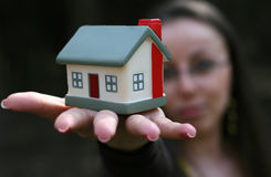 Woman offering a house. Woman holding house on hand Royalty Free Stock Photography