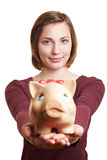 Woman offering piggy bank. Smiling attractive woman offering big piggy bank Stock Photo