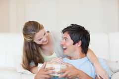 Woman offering a present to her boyfriend Stock Images