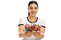 Woman offering a small shopping basket Stock Photo