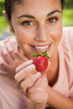 Woman offering a strawberry while lying in grass Stock Photography