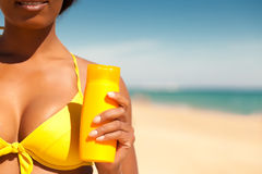 Woman offering suncream on beach Stock Photo
