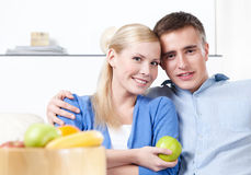 Woman offers an apple to her husband Stock Photography