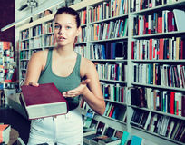 Woman offers a book in a bookstore Stock Images