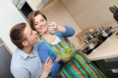 Woman offers her husband to taste salad Royalty Free Stock Images