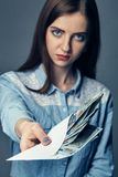 The person`s hand gives a bribe in dollars. American dollars in hand. Woman offers money on a dark background. A pile of. Woman offers money on a dark background Stock Photography