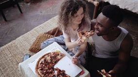 Woman offers pizza to man, but eat slice by herself. Multiracial couple having fun during the meal with fast food. Caucasian female in pajamas feeds the royalty free stock photography
