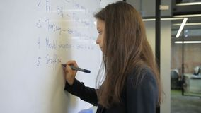 Woman in an office on blackboard by marker writing text in English. During seminar female employee writes important information for planning business processes stock footage