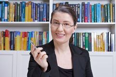 Woman office books lesson e-learning. Friendly middle aged woman with black blazer in an office with lots of books explaining something during an online lesson Royalty Free Stock Photo