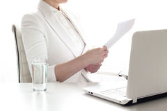 Business woman working  at office. Closeup of woman  at office desk, working with computer, reading paper, document or contract. Glass of water on table Royalty Free Stock Photography