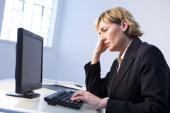 Woman in office on computer Stock Image