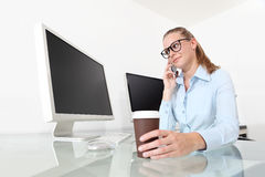 Woman in office at desk in front of computer screen, talking on Stock Images
