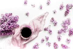 Woman office desk with scarf, coffee and lilac blossom design white background top view stock photo