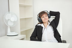 Woman at office with ear-phones and listens to m Stock Images