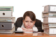 Woman in office with folder stacks is desperate, s. Tressed and over-worked. Isolated on white background Royalty Free Stock Images