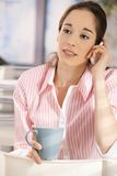 Woman in office having coffee and phone call Stock Photography