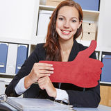 Woman in office holding red thumbs Royalty Free Stock Photo