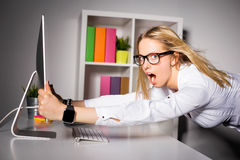 Woman in office holding on to computer Stock Photo