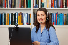 Woman office hotline helpdesk callcenter. Friendly smiling woman with computer, webcam and headphone at a callcenter, hotline or helpdesk Stock Images