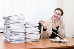 Woman in office interior speaking by telephone Royalty Free Stock Photos