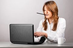 Woman at office with laptop Stock Images
