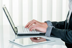 Woman in office with laptop computer com Stock Images
