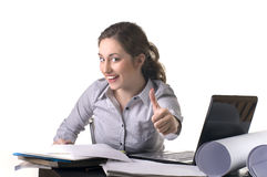 Woman at office with laptop giving thumbs-up-sign Royalty Free Stock Photo