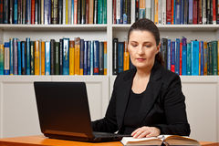 Woman office laptop reading book. Mature woman in an office or library with her laptop reading in a book, advocate, lawyer, teacher, prof, historian Stock Images