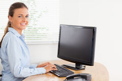 Woman in office looking while typing Stock Photography