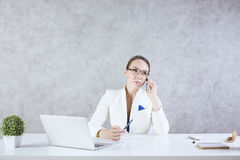 Woman in office on phone Royalty Free Stock Photos