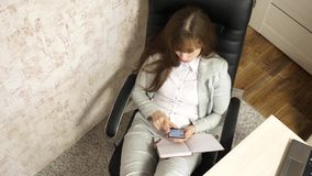 Woman in office resting in workplace. beautiful businesswoman with phone sits in a chair with bare feet on the table. Resting. a girl at work in the office stock video footage